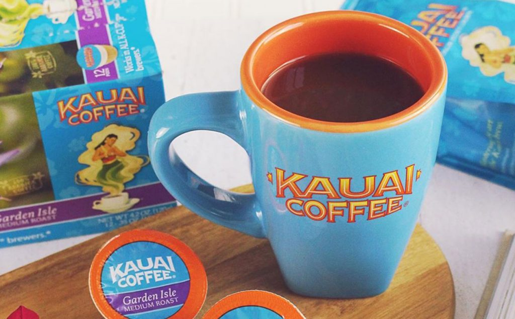 Blue Kauai Coffee mug sitting on a wooden platter with single-serve cups and boxes of coffee in the background