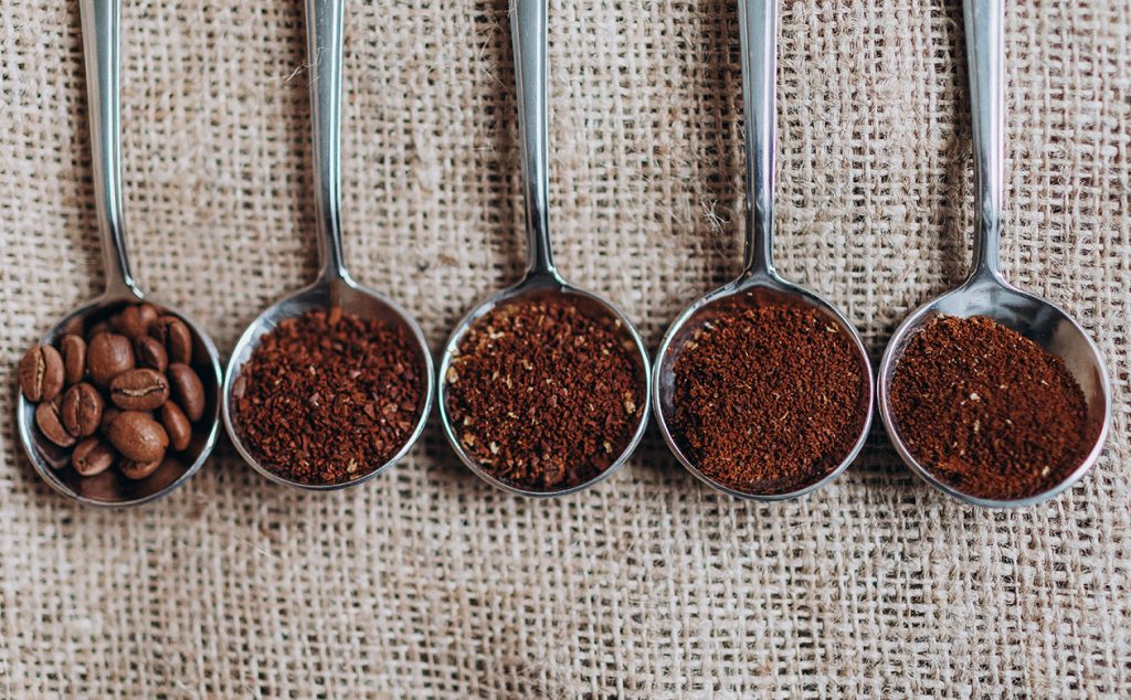 Five metal spoons sitting on a burlap cloth. Each spoon contains a different grind size from whole bean to espresso. Learn how to grind coffee beans like a pro with the Kauai Coffee grind guide