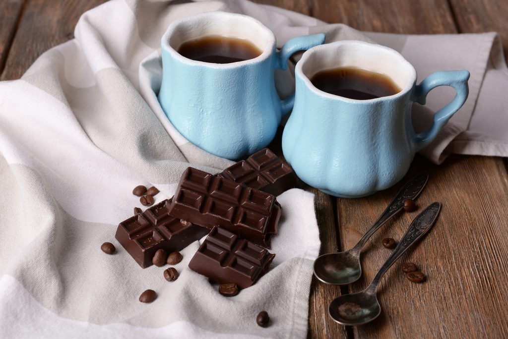 kauai chocolate and coffee festival. image of two blue mugs filled with coffee and chocolate bars on a table.