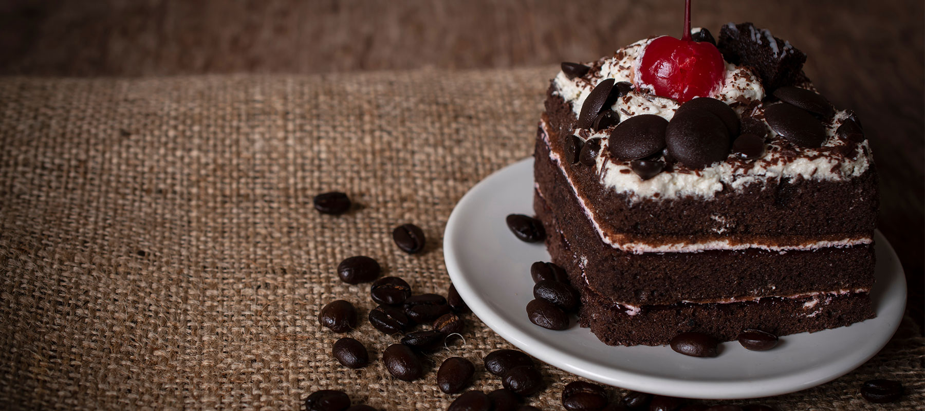shutterstock image of chocolate cream cake sitting on a table covered in a burlap coffee bag with coffee beans sprinkled around