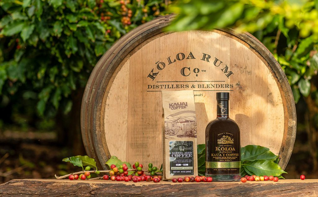 Kauai Coffee Rum Barrel Aged Coffee and Koloa Kauai Coffee Rum make gread additions to holiday cocktails. A bag of coffee and bottle of rum sit on a barrel in the coffee field. Red cherries are on the branches and on the barrel