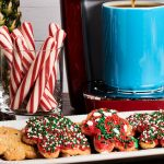 iced sugar cookies sit on a white serving platter in the foreground. In the background a red single serve coffee maker fills a blue ceramic mug with coffee. A glass with peppermint sticks and a pineapple is also visible in the background.