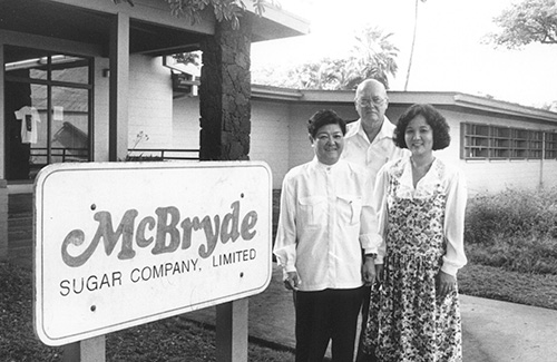 kauai coffee company began as the mcbryde sugar company. this is a historical photo of staff standing in front of the mcbryde sugar sign