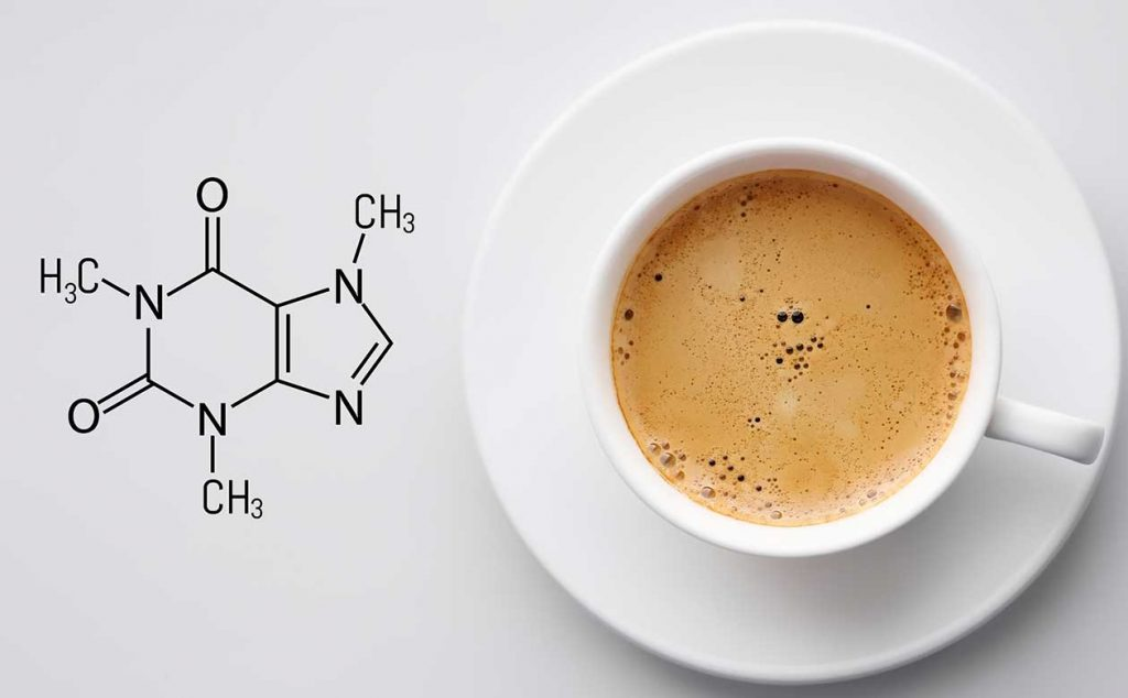 A birdseye view of a cup of coffee on a white background. A diagram of the caffeine molecule is superimposed on the white surface next to the coffee cup.