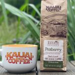 a bag of kauai coffee peaberry coffee sits on a wooden table with a white kauai coffee mug next to it. Greenery is visible in the background