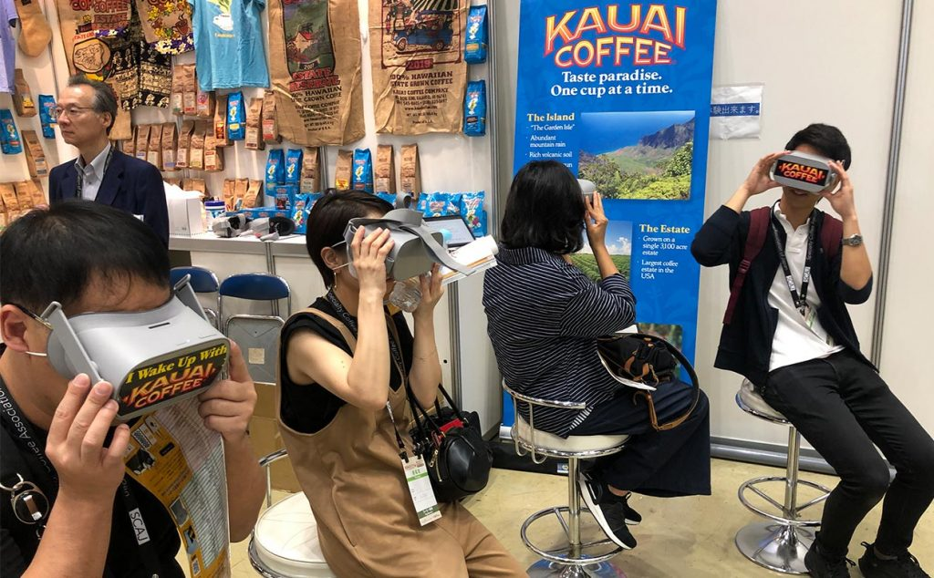 Visitors to the kauai coffee booth at the specialty coffee conference in tokyo japan take a virtual 360 degree tour.