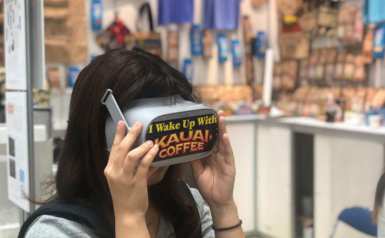 Kauai Coffee booth visitor at the Specialty Coffee Association Conference and Exhibition in Tokyo Japan takes virtual tour of estate.