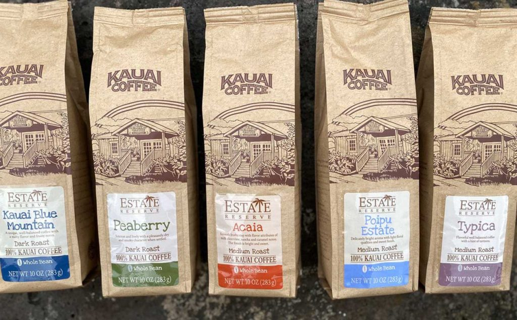 Five bags of Kauai Coffee Estate Reserve varieties lay on a lava rock background. A Bag of Acaia is pictured in the middle